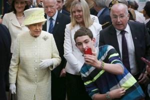 BELFAST, NORTHERN IRELAND - JUNE 24: ילד מפתיע את המלכה על צילום סלפי בעת ביקור רשמי בבלפסט בינואר 2015.